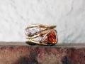 Ring 5 - Vågring i rödguld med vitguldsfattningar runt diamant och spessartingranat